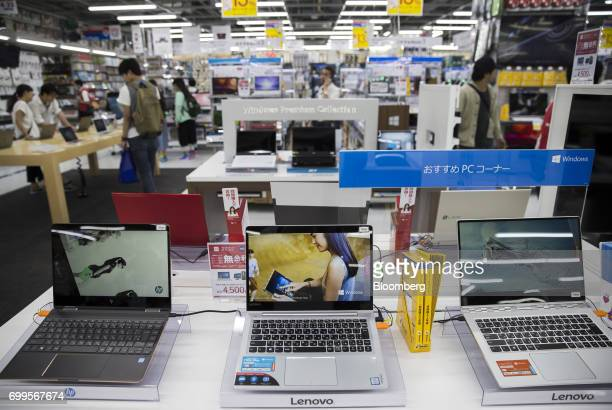 An HP Inc left and Lenovo Group Ltd laptop computers are displayed for sale at the Bic Camera Akiba electronics store operated by Bic Camera Inc in...