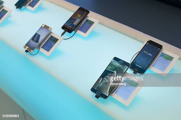 An HTC One A9 smartphone manufactured by HTC Corp right sits above a Samsung Galaxy S6 mobile device manufactured by Samsung Electronics Co inside a...