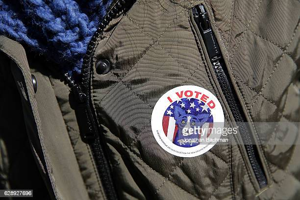 An I Voted sticker featuring local Louisiana artist George Rodrigue's Blue Dog is worn by a voter on December 10 2016 in New Orleans Louisiana...