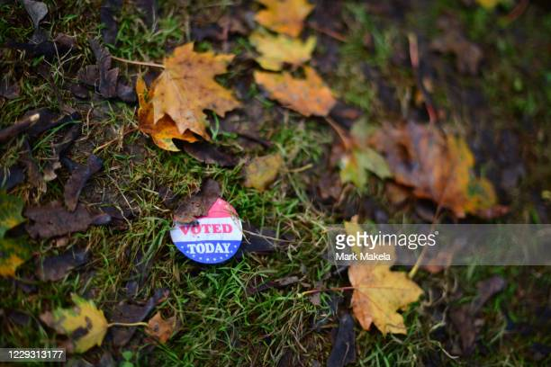 "An ""I VOTED TODAY"" sticker lies amid fallen maple leaves outside of an early voting satellite polling location on October 27, 2020 in Philadelphia,..."