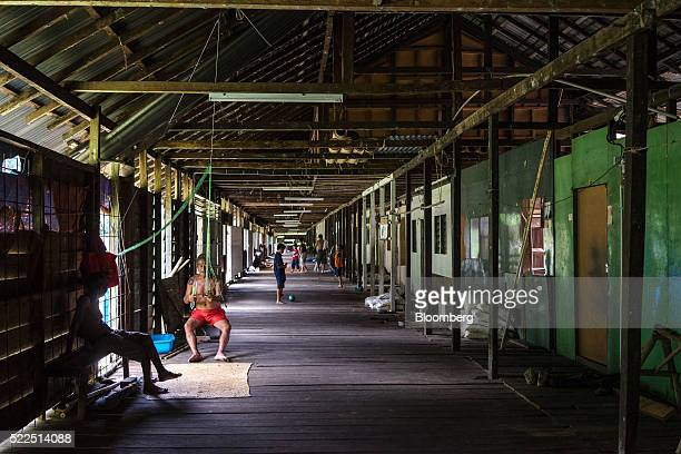 An Iban man repairs a fishing net as a child plays soccer in the public area of a traditional longhouse in the village of Ensika in Simunjan district...