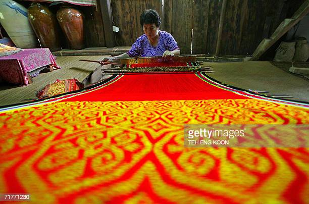 An Iban woman weaves pua kumbu in her longhouse at the Cultural Village in Sarawak the largest state in Malaysia located on the southwestern of...