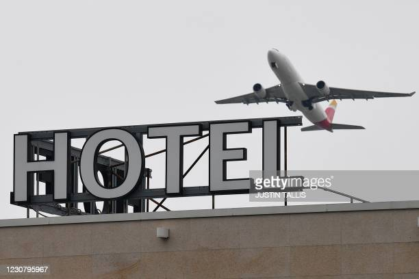 An Iberia Airbus A330 is seen flying over a hotel at Heathrow Airport in west London on January 26, 2021. - The British government is being urged to...