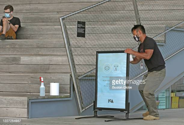 An ICA employee cleans a sign reminding visitors to wear coverings and social distance at the Institute of Contemporary Art in Boston's Seaport...