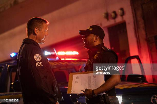 An ICE agent with US Homeland Security Investigations and a Guatemalan policeman speak at the scene of a raid where a suspected human trafficker was...