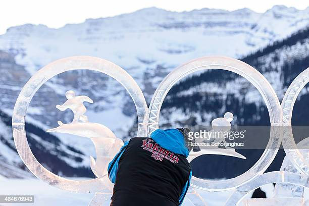 An ice carver works on his unfinished ice sculpture at the 2014 Lake Louise Ice Magic festival, with the Victoria Glacier and Lake Louise visible in...
