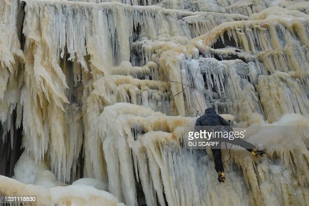 An ice climber ascends Kinder Downfall, a frozen waterfall in the Peak District National Park near Hayfield, northwest England as snow blankets the...