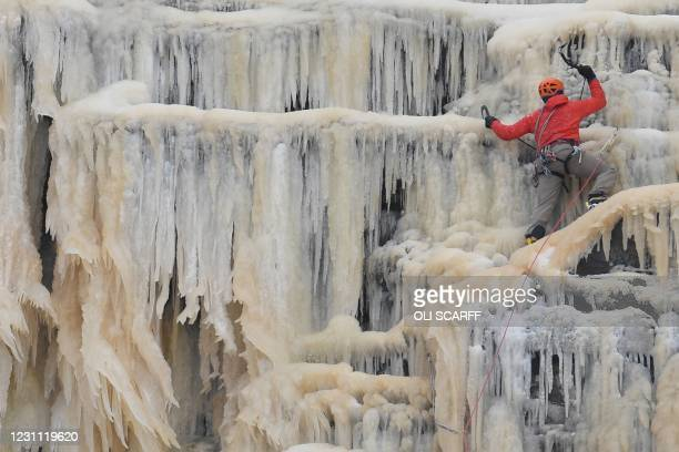 An ice climber ascends Kinder Downfall, a frozen waterfall in the Peak District National Park, near Hayfield, northwest England as snow blankets the...