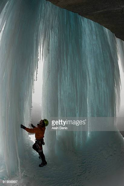 An ice climber in looks at a new climbing route on blue, frozen waterfall, Icefield Parkway, Alberta