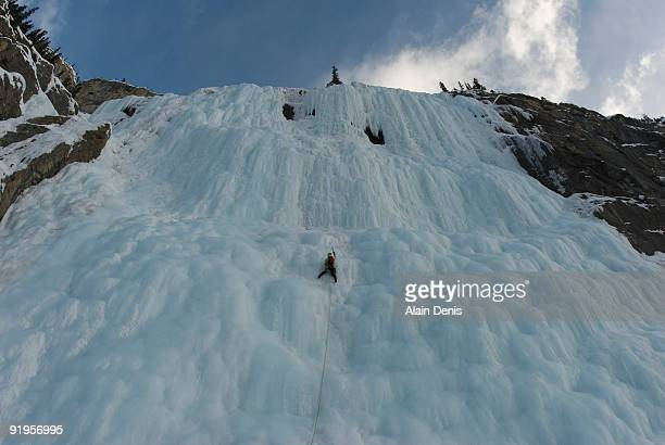 An ice climber in the middle of a massive frozen waterfall, the Weeping Wall, Icefield Parkway, Albe