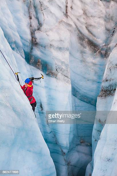 An ice climber swings his ice tools in a moulin on the Root Glacier in Wrangell-St. Elias National Park, Alaska.