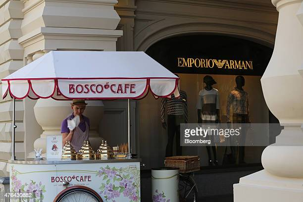 An ice cream seller operates a Bosco Cafe branded stall outside an Emporio Armani fashion store at the entrance to the GUM luxury department store in...