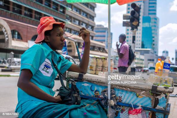 An ice cream vendor looks on as she waits for customers along Jason Moyo street in central Harare on November 20 2017 Zimbabwe is locked in one of...