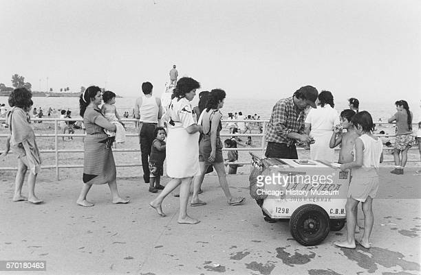An ice cream vendor selling ice cream and popsicles while beachgoers pass in Calument Park Chicago Illinois August 2 1987