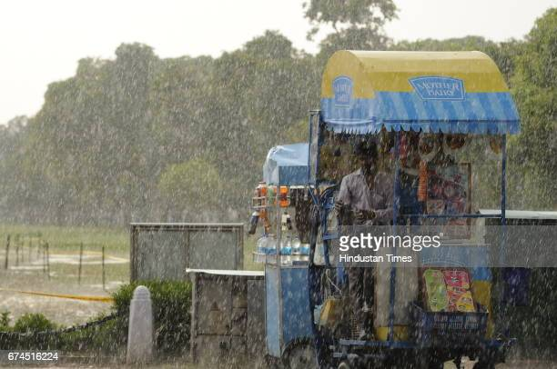 An Ice cream vendor takes shelter during a sudden downpour on April 28 2017 in New Delhi India