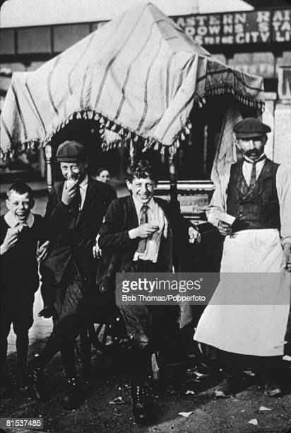 An ice cream vendor with three satisfied customers outside Hackney Downs Station in London circa 1905