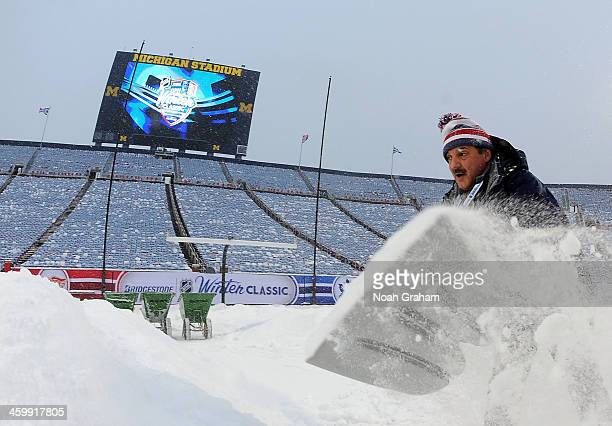 An ice crew member shovels snow during the 2014 Bridgestone NHL Winter Classic on January 1, 2014 at Michigan Stadium in Ann Arbor, Michigan.