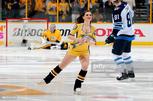 An ice girl carries away a catfish prior to the first period between the Nashville Predators and the Winnipeg Jets in Game One of the Western...