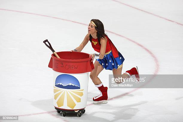 An Ice Girl pushes a trash container and shovel across the ice during a break in play between the Detroit Red Wings and the Calgary Flames on October...