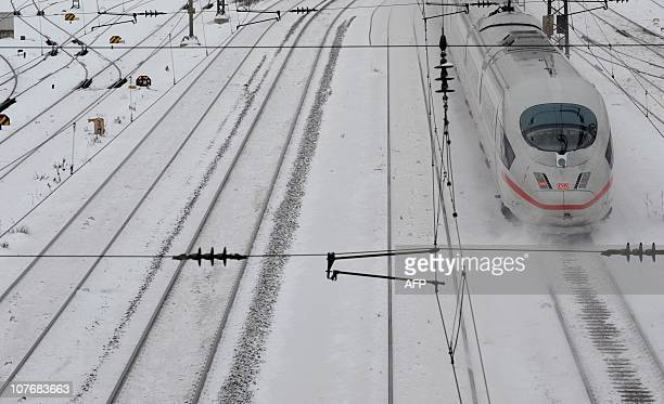 An ICE highspeed train makes its way over snowy railtracks near Munich's main railway station on December 2 2010 Weather brought snow falling across...