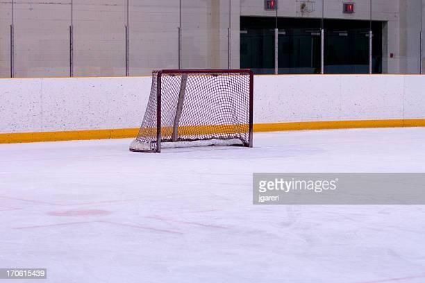Une patinoire avec des lignes jaunes sur le mur et un filet de hockey sur glace