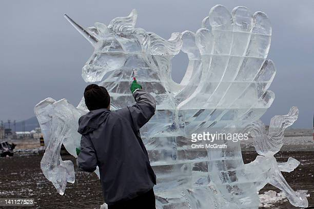 An ice sculptor works to complete a unicorn piece for the anniversary of last year's deadly earthquake and tsunami in the early morning hours of...