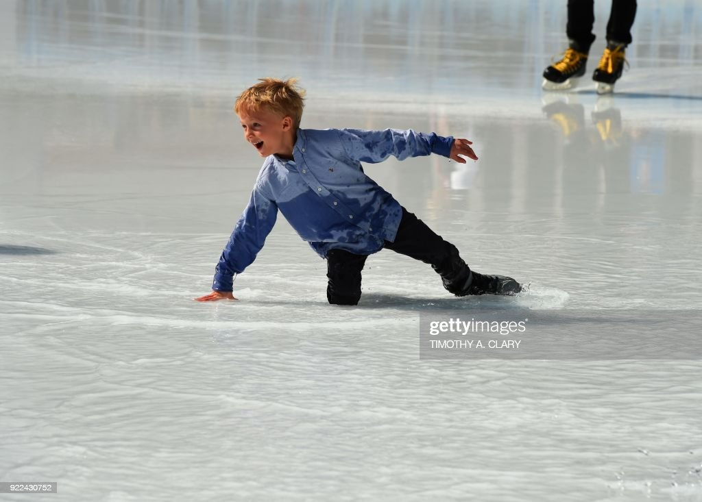 An ice skater falls in the water from the melted ice at the Bryant Park Ice Skating Rink in Braynt Park February 21, 2018 as New York City hit record highs with temperatures stretching into the 70's. /
