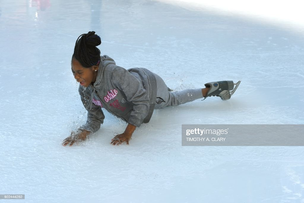 An ice skater falls in the water from the melted ice at the Bryant Park Ice Skating Rink on February 21, 2018