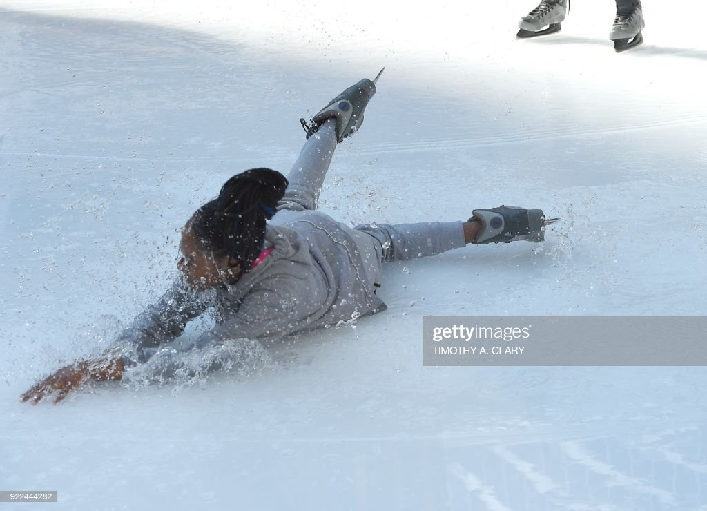 An ice skater falls in the water from the melted ice at the Bryant Park Ice Skating Rink on February 21, 2018. New York reached record high temperatures on Wednesday. At noon, the temperature had reached 72F (22C) in the city, surpassing the record of 68F (20C) set in 1930. /
