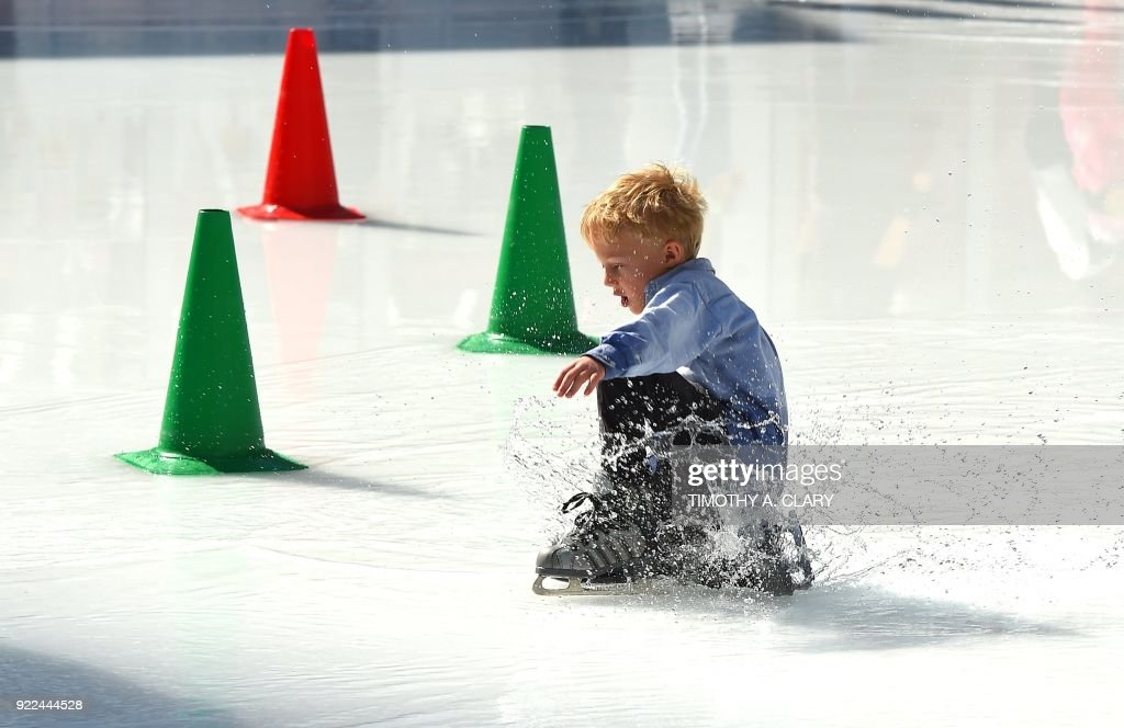 An ice skater falls in the water from the melted ice at the Bryant Park Ice Skating Rink on February 21, 2018 New York reached record high temperatures on Wednesday