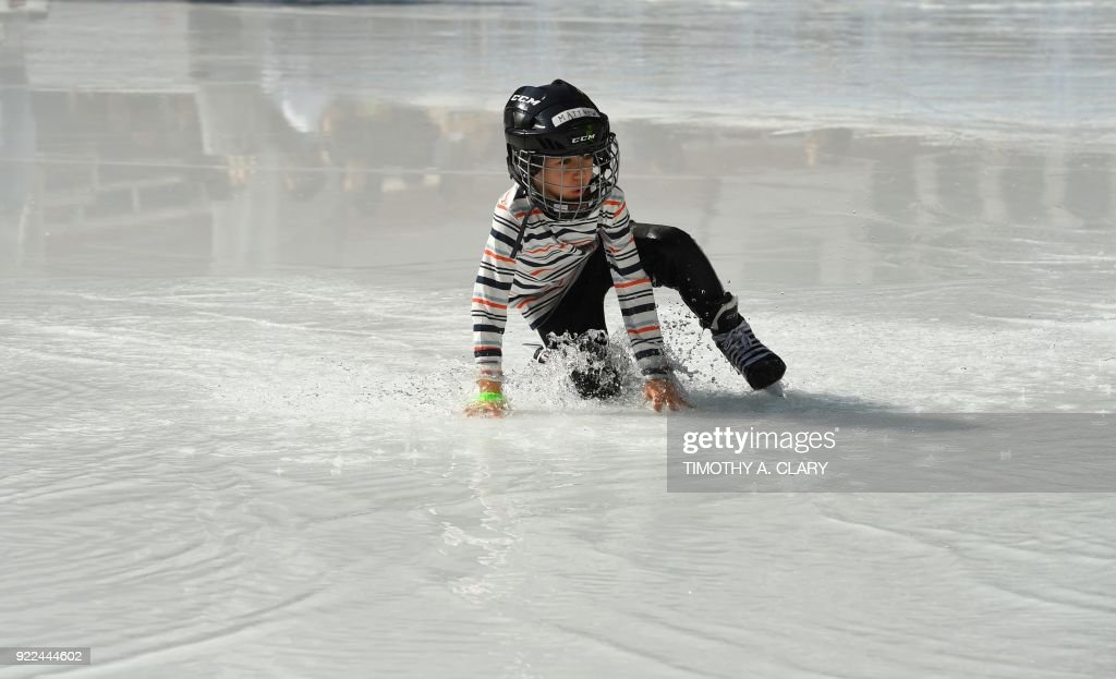 An ice skater falls in the water from the melted ice at the Bryant Park Ice Skating Rink on February 21, 2018 New York reached record high temperatures on Wednesday. At noon, the temperature had reached 72F (22C) in the city, surpassing the record of 68F (20C) set in 1930. /
