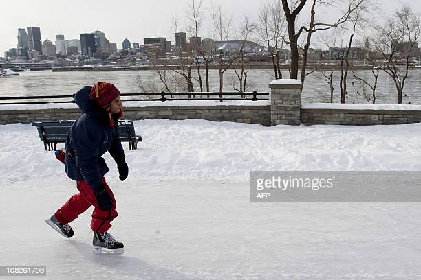 An Ice skater glides on a trail next to the frozen St Lawrence River during La fête des Neiges Montréal's great winter festival where families are...