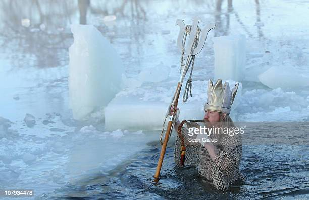 An ice swimming enthusiast dressed as Neptune takes to the frigid waters of Orankesee lake during the 27th annual 'Winter Swimming in Berlin' on...
