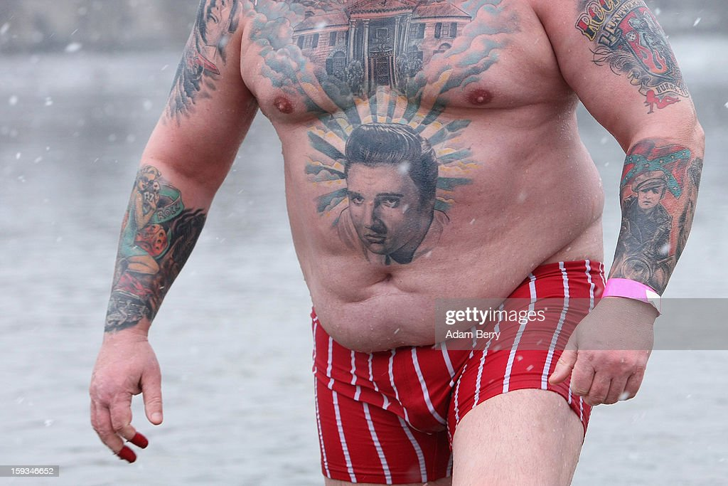 An ice swimming enthusiast with a tattoo of Elvis wades in the cold waters of Orankesee lake during the 'Winter Swimming in Berlin' event on January 12, 2013 in Berlin, Germany. A local swimmers' group called the 'Berlin Seals' invite ice swimmers from across Germany and abroad to the annual event, which, despite warmer temperatures this winter and a lack of ice, was still held. Members claim ice swimming is good for the body's blood circulation.