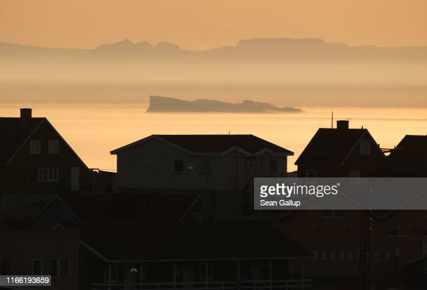 An iceberg floats in Disko Bay at sunset behind houses on August 04 2019 at Ilulissat Greenland The Sahara heat wave that recently sent temperatures...