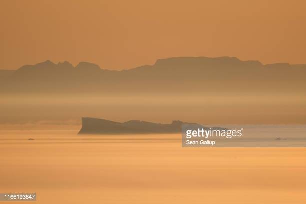 An iceberg floats in Disko Bay at sunset on August 04 2019 near Ilulissat Greenland The Sahara heat wave that recently sent temperatures to record...