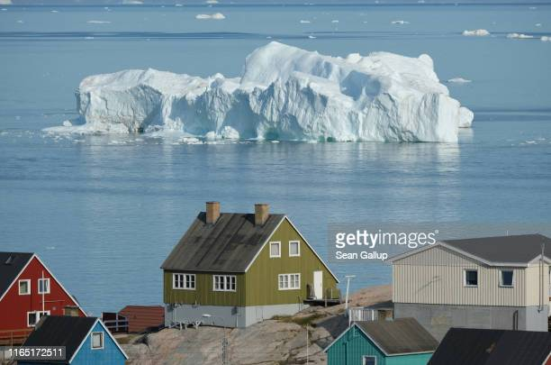An iceberg floats in Disko Bay behind houses during unseasonably warm weather on July 30, 2019 in Ilulissat, Greenland. The Sahara heat wave that...