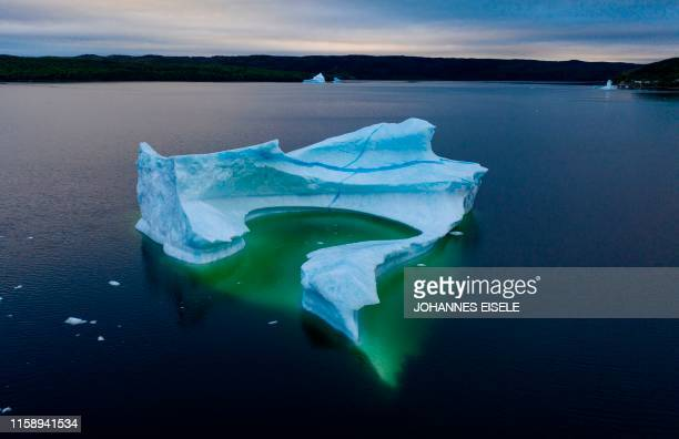 An iceberg floats near the seashore of King's Point on July 5 2019 in Newfoundland Canada Formerly the center of cod fishing the island province now...