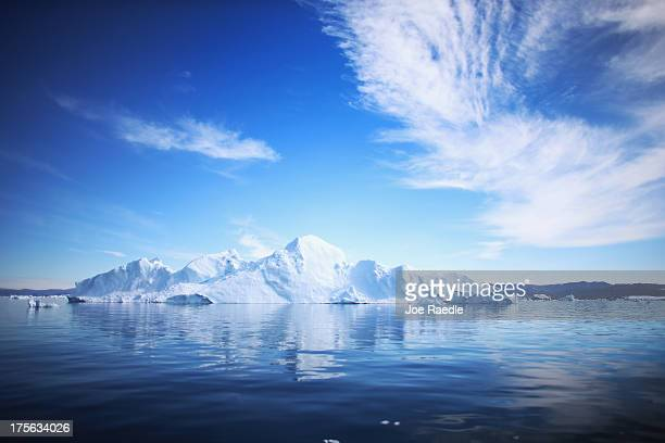 An iceberg floats through the water on July 20 2013 in Ilulissat Greenland As Greenlanders adapt to the changing climate and go on with their lives...
