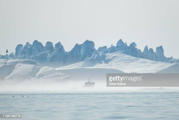 An iceberg looms behind a boat carrying tourists at the mouth of the Ilulissat Icefjord on August 04 2019 near Ilulissat Greenland The Sahara heat...
