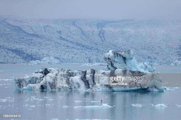 An iceberg that has broken off of receding Breidamerkurjokull glacier, which looms behind, floats on Jokulsarlon lake on August 15, 2021 near Hof,...