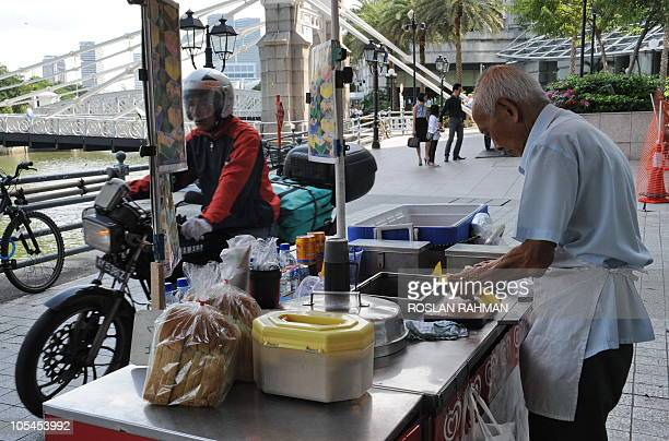 An icecream vendor prepares for a day's work on the street in the financial district of Singapore on October 14 2010 Singapore's economy is on track...
