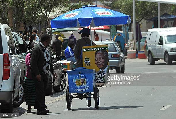 An icecream vendor rides with a poster of Nelson Mandela near the Mandela House in Soweto near Johannesburg on December 7 two days after Mandela's...