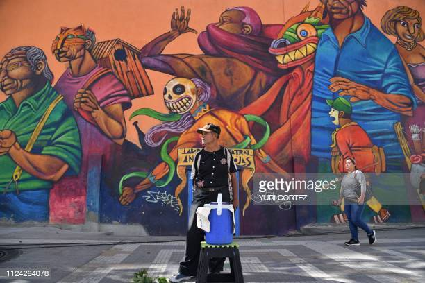 TOPSHOT An icecream vendor stands in front of a mural in the centre of Caracas on February 12 2019 A tug of war between the Venezuelan government and...