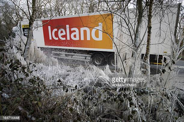 An Iceland supermarket lorry passes a section of icicles and icecovered hedgerow caused by a water splashed from the roadside near Hazeley Bottom...