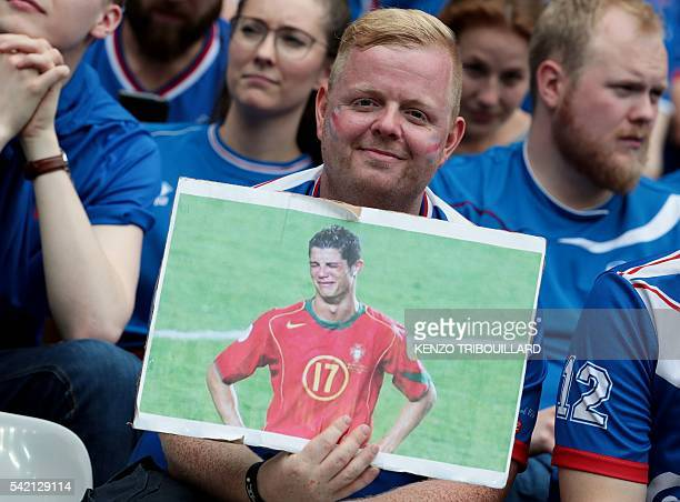 An Iceland supporter holds a picture depecting Portugal's forward Cristiano Ronaldo before the Euro 2016 group F football match between Iceland and...