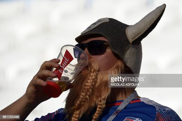 An Iceland's fan sporting a fake Viking helmet drinks beer as he waits in the grandstand before the Russia 2018 World Cup Group D football match...