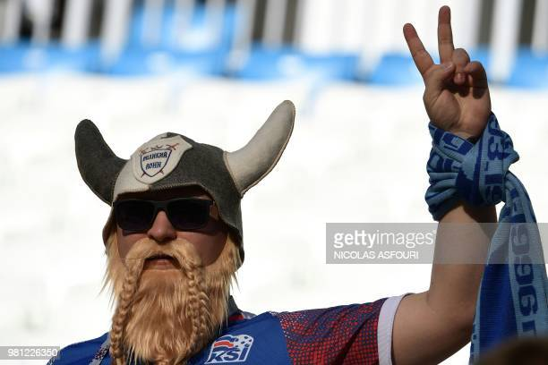 An Iceland's fan sporting a fake Viking helmet flashes the Victory sign as he waits in the grandstand before the Russia 2018 World Cup Group D...
