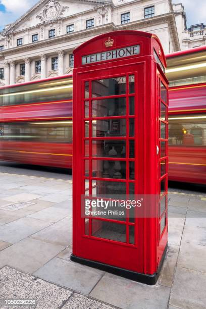 An iconic red London bus passes by an Iconic London Phone booth