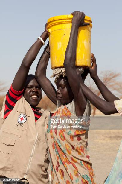 An ICRC worker assists a woman collecting water at Wara village in Pariang County Unity State South Sudan where the International Committee of the...